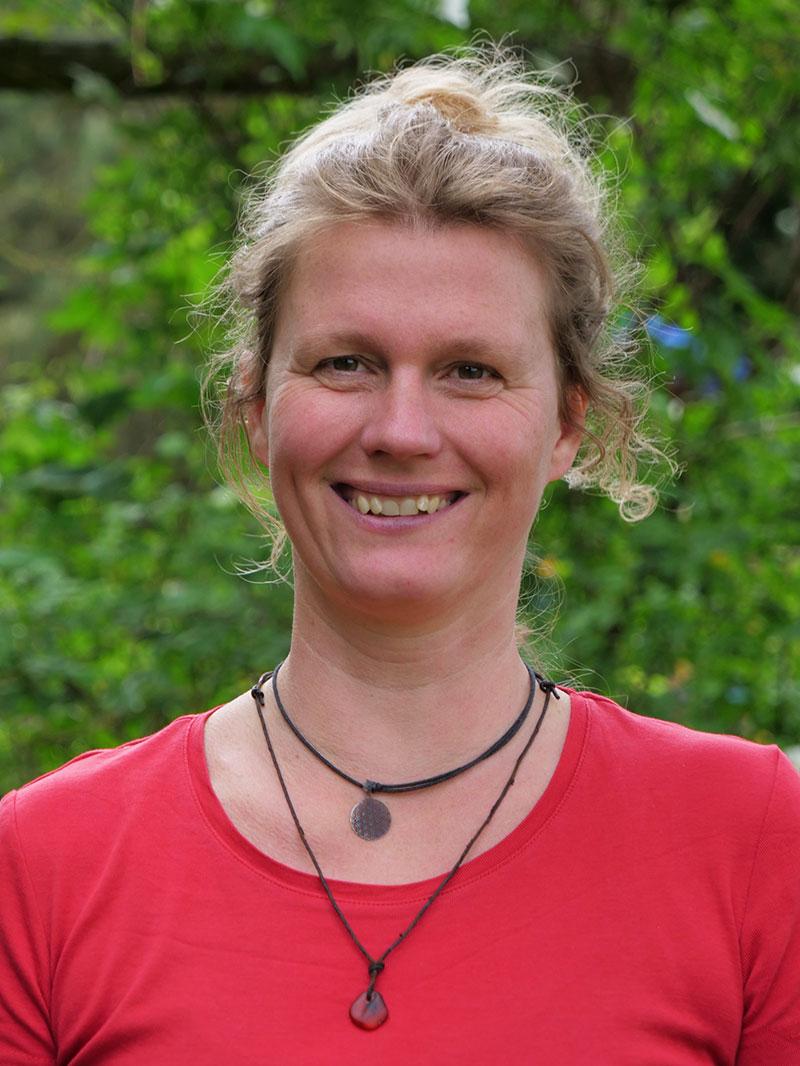 Doreen Duelli vor einer grünen Blätterwand in einem roten Oberteil und einer Kette um den Hals