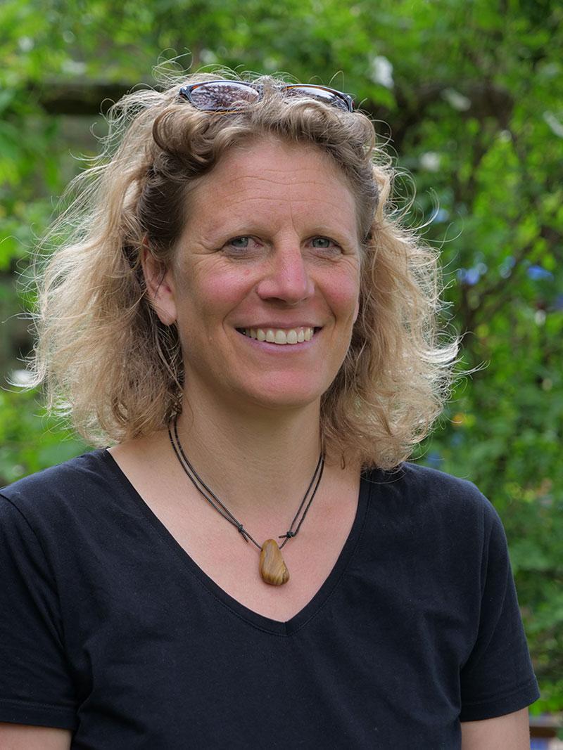 Maritta Vierlinger vor grünem Hintergrund in einem schwarzen Oberteil und mit einer kette um den Hals